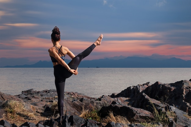 De aziatische vrouw die een yoga doet stelt voor saldo en het uitrekken zich.