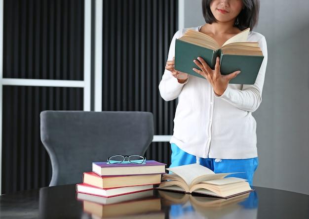 De aziatische vrouw die en opent een boek houden om in bibliotheek te lezen.