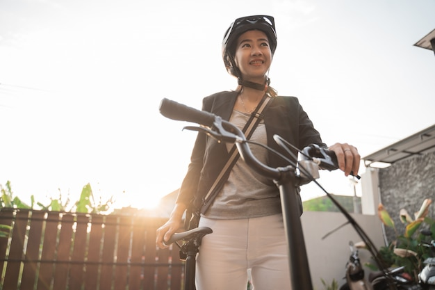De aziatische vrouw die helm en zak dragen bereidt een vouwfiets van haar huis voor om te gaan werken