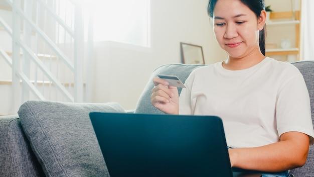 De aziatische vrouw die laptop, creditcard met behulp van koopt en koopt elektronische handel internet in woonkamer van huis