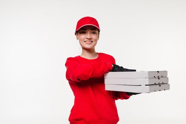 De aziatische vrouw die van de pizzalevering een pizza houdt over geïsoleerd op witte muur