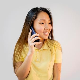 De aziatische vrouw die van smiley op de telefoon spreekt