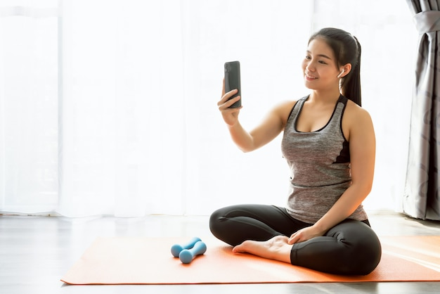 De aziatische vrouw die van smiley sportkleding draagt die oranje mat zit en een foto van zich neemt terwijl het uitoefenen.