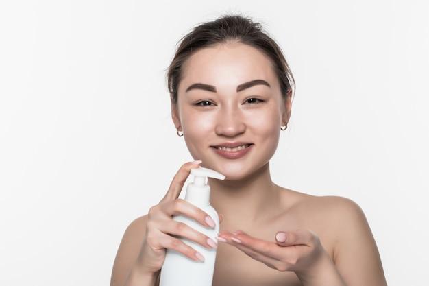 De aziatische vrouw drukt de handlotion die op witte muur wordt geïsoleerd.