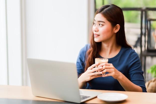 De aziatische vrouw gebruikend computerlaptop en drinkt het koffiewerk van huisconcept