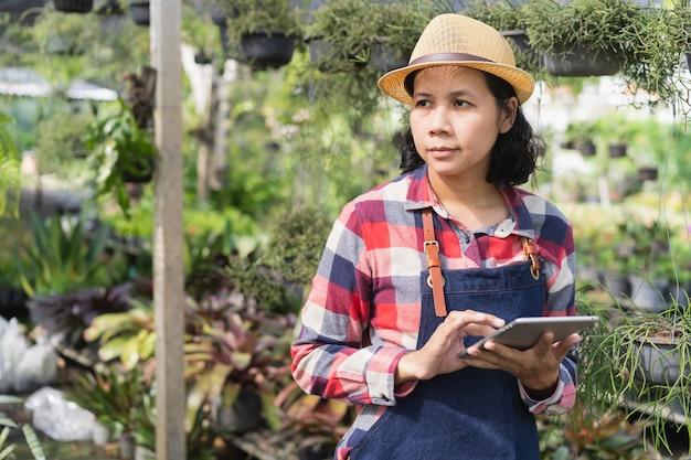 De aziatische vrouw gebruikt een tablet om de vegetatie in de sierplantwinkel te controleren, klein bedrijfsconcept