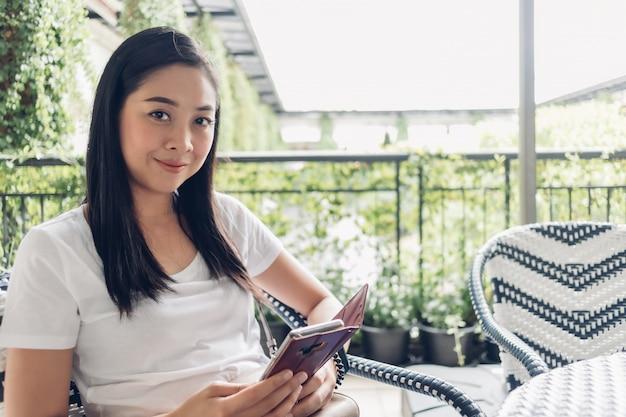 De aziatische vrouw gebruikt haar smartphone terwijl het zitten in koffie.