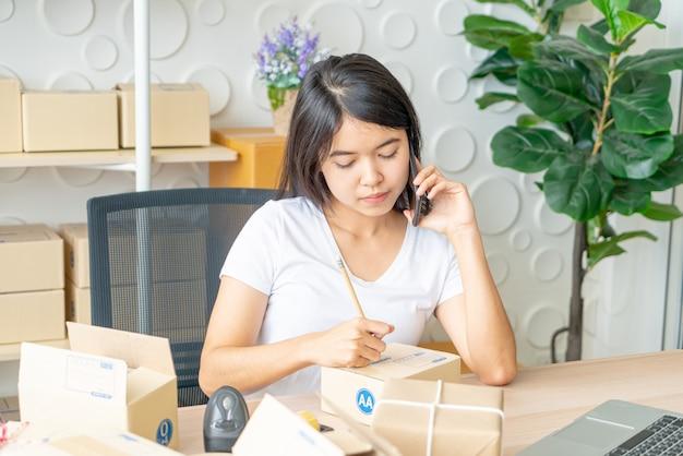 De aziatische vrouw geniet van terwijl het gebruiken van internet op laptop en telefoon in bureau