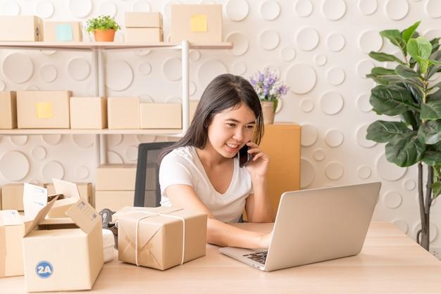 De aziatische vrouw geniet van terwijl het gebruiken van internet op laptop en telefoon op kantoor