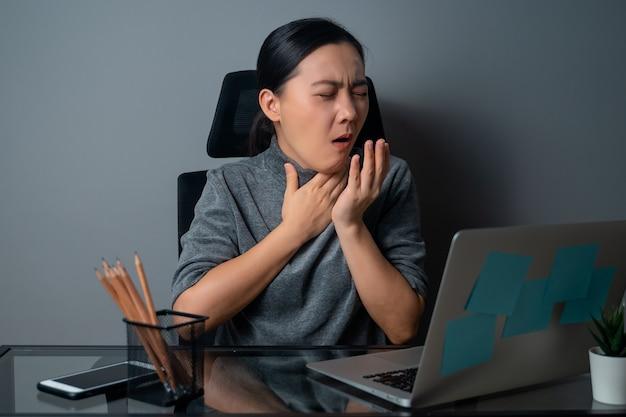 De aziatische vrouw had koorts en werkte op kantoor op een laptop