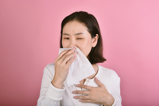 De aziatische vrouw heeft keelpijnallergie en hoest in papieren zakdoekje.