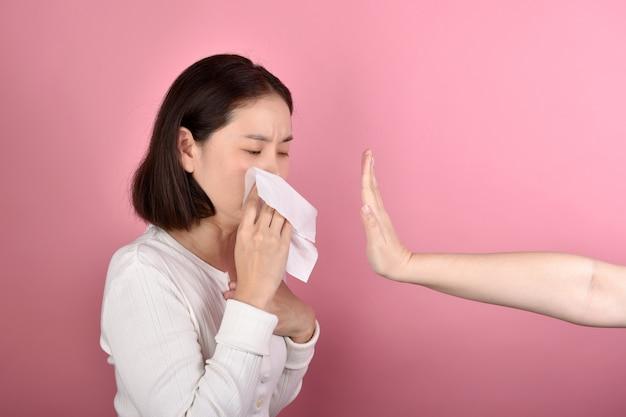 De aziatische vrouw heeft keelpijnallergie en hoest in papieren zakdoekje