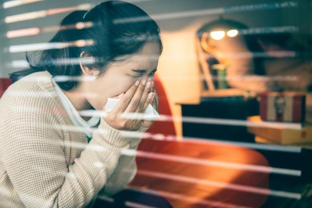 De aziatische vrouw heeft verkoudheid, gebruikt een tissue om haar mond te bedekken bij hoesten en niezen thuis, om de verspreiding van virus covid 19, gezondheidszorgconcept te voorkomen. selectieve en zachte focus.