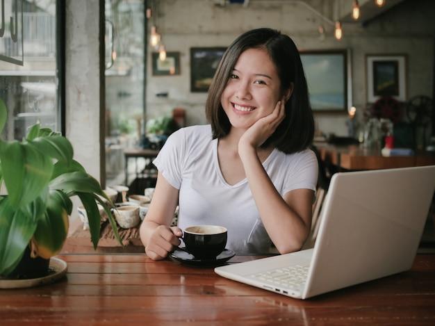 De aziatische vrouw het drinken koffie en ontspant in de koffie van de koffiewinkel