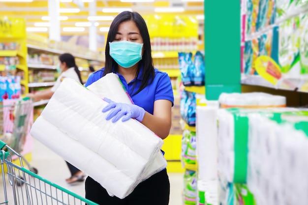 De aziatische vrouw in medisch gezichtsmasker en medische handschoenen kiest toiletpapier in supermarkt