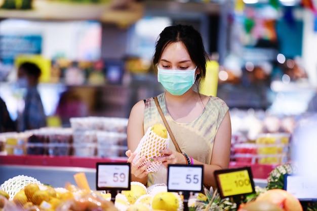 De aziatische vrouw in medisch gezichtsmasker kiest vruchten terwijl het winkelen in supermarkt. coronavirus concept