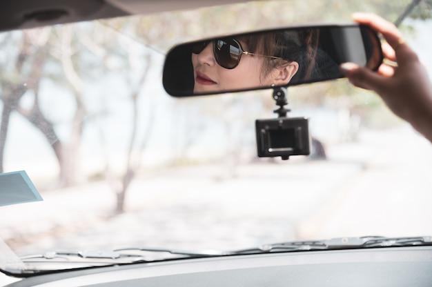 De aziatische vrouw in wit overhemd onderzoekt de spiegel en glimlacht terwijl het zitten in haar auto