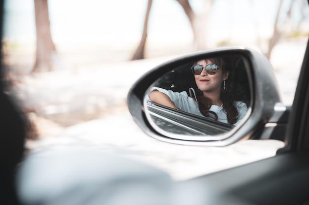 De aziatische vrouw in wit overhemd onderzoekt de zijaanzichtspiegel en glimlacht terwijl het zitten in haar auto, reisconcept.