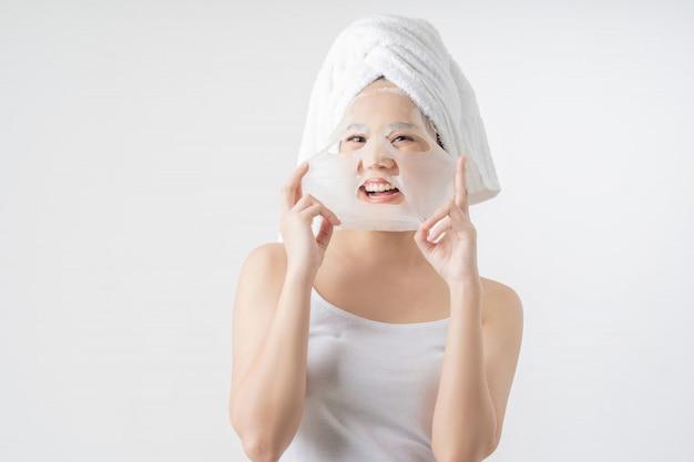 De aziatische vrouw is gezichtsmaskerblad. ze is blij en verrast.