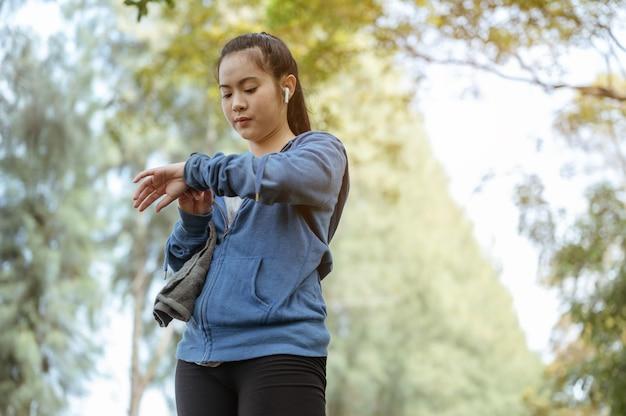De aziatische vrouw keek naar de klok en drukte op de klokstop nadat ze naar het park was gerend