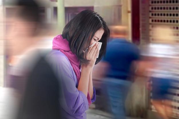 De aziatische vrouw krijgt griep die terwijl openlucht lopen niezen