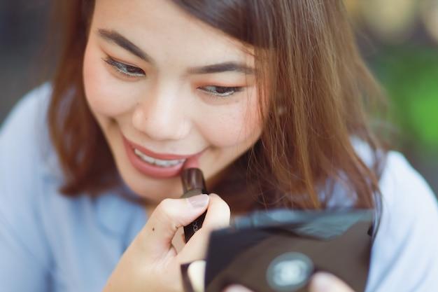 De aziatische vrouw maakt omhoog haar gezicht met lippenstift in koffie