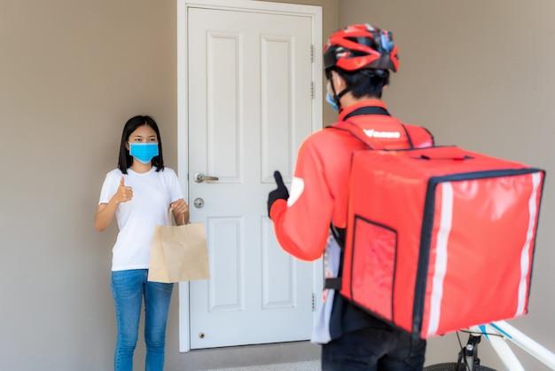 De aziatische vrouw neemt de zak van het leveringsvoedsel op van deurknop en duim omhoog contactloos of contact vrij van bezorger met fiets vooraan huis voor sociale afstand voor besmettingsrisico. coronavirus concept