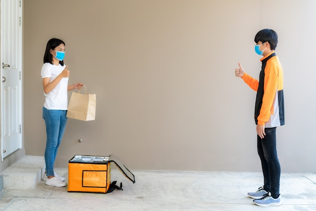 De aziatische vrouw neemt de zak van het leveringsvoedsel van doos op en duim omhoog contactloos of contact vrij van leveringsruiter met fiets vooraan huis voor sociale afstand voor infectierisico.