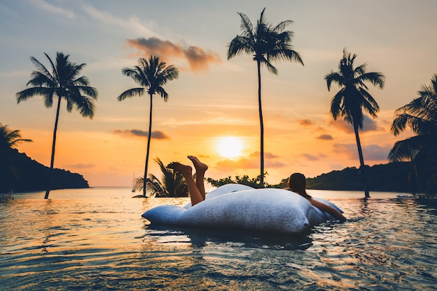 De aziatische vrouw ontspant in pool op strand in zonsondergang in thailand