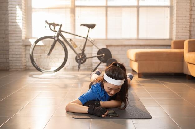 De aziatische vrouw ontspant van fietsoefening in huis. ze speelt telefoon
