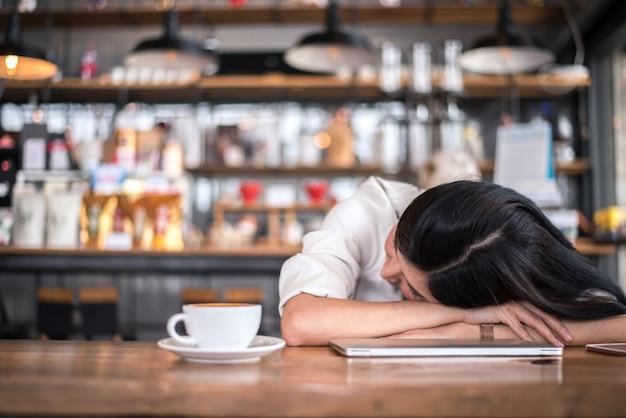De aziatische vrouw rust en slaapt in een koffiewinkel omdat zij van het werken beu is