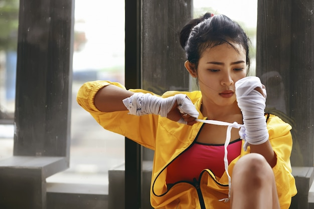 De aziatische vrouw van de schoonheid in geel jasje verpakt haar pols