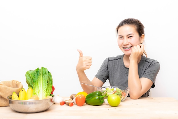 De aziatische vrouw van haapy met tandsteunen die duim tonen terwijl het eten van saladegroente op wit