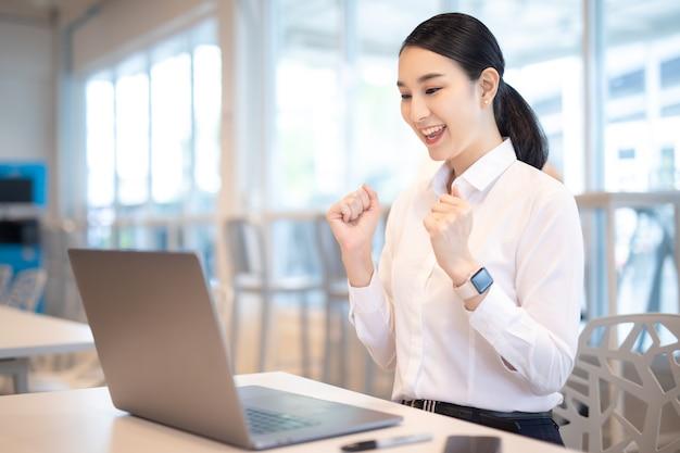 De aziatische vrouw viert met laptop, stelt het gelukkige succes.