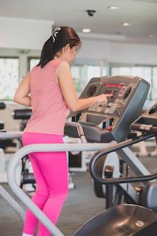 De aziatische vrouw werkt oefening bij gymnastiekgewichtsverlies uit