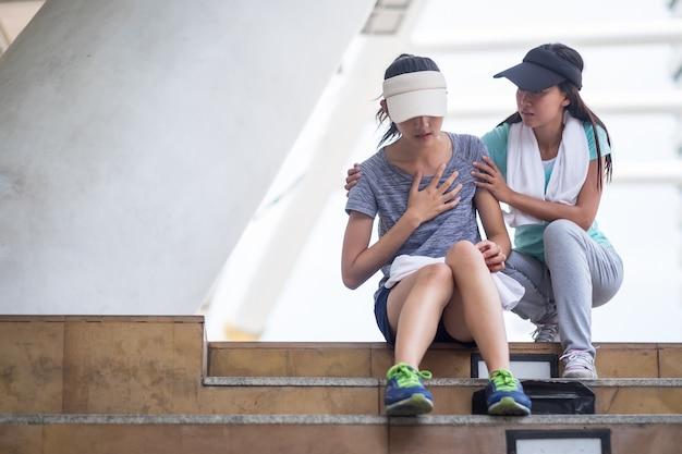 De aziatische vrouw wordt geprobeerd na het joggen. over oefening