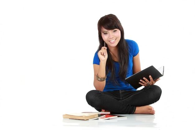 De aziatische vrouw zit en schrijft een boek