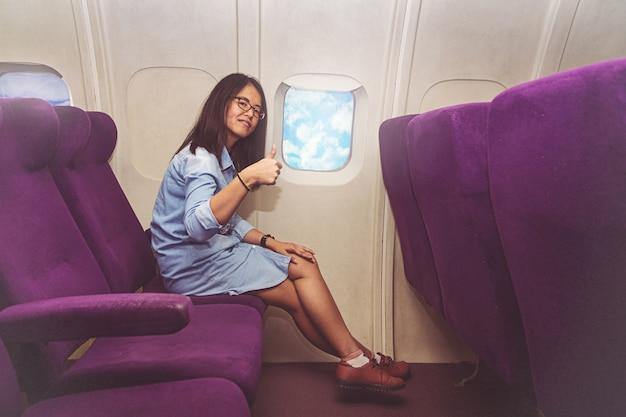 De aziatische vrouw zit in het vliegtuig en toont duim