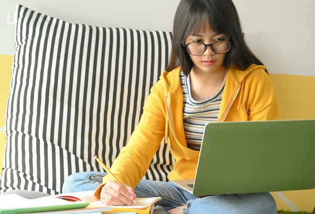 De aziatische vrouwelijke student die glazen draagt onderzoekt laptop en neemt nota's om een rapport te maken.