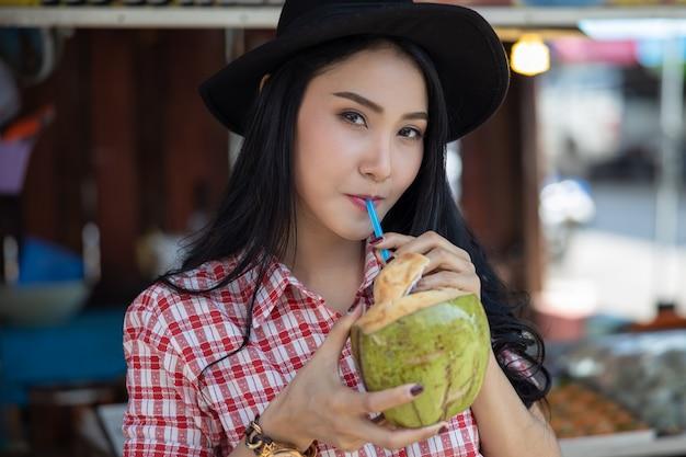 De aziatische vrouwelijke toerist drinkt kokosnotenwater bij amphawa watermarkt