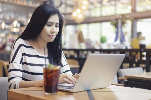 De aziatische vrouwen die computerlaptop gebruiken werken nieuwe projectzitting alleen bij koffie.