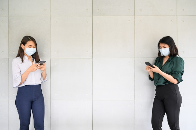 De aziatische vrouwen die gezichtsmasker dragen gebruikend smartphone en houden sociale afstand