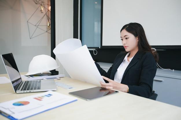 De aziatische vrouwen die holdingsblauwdrukken ontwerpen en hebben bouwvakker op lijst voor het werken op kantoor
