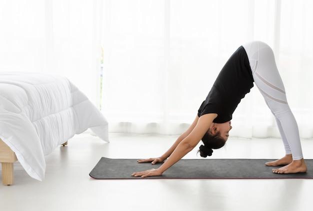 De aziatische vrouwen die yogaoefening thuis doen, die bij naar beneden toegekeerde hond uitrekken stellen zich of adhomukha svanasana in witte slaapkamer.
