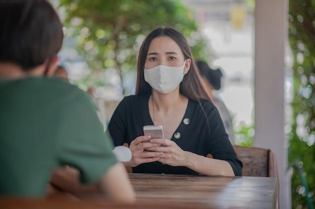 De aziatische vrouwen gebruiken de zitting van het gezichtsmasker in restaurant zachte nadruk, nieuw normaal concept