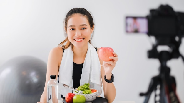 De aziatische vrouwen gezonde blogger toont fruit en schoon dieetvoedsel. voor de camera om live videostreaming van vlogvideo thuis op te nemen.fitness influencer op sociale media online.