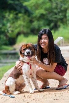 De aziatische vrouwen met gemengde rassenhond in bruin