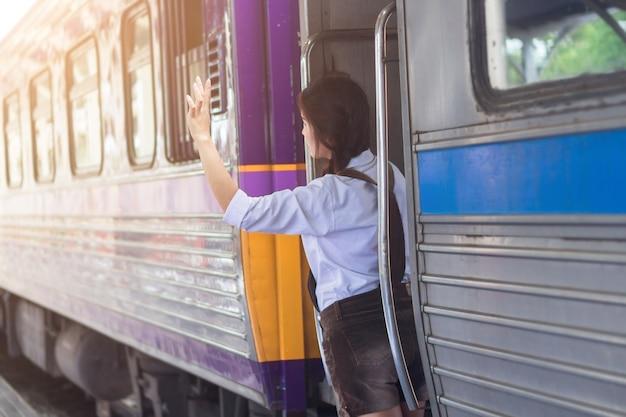 De aziatische vrouwen zwangere hand zegt omhoog hello en rode zak op het trainstation van de treinreis