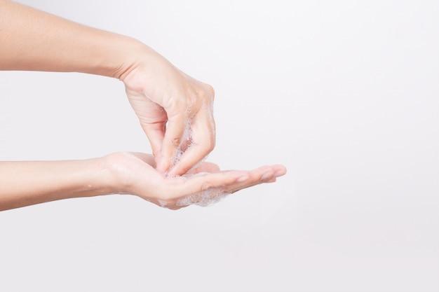 De aziatische vrouwenhand wast met zeepbels op wit