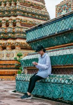 De aziatische vrouwenreiziger zit en controleert foto in camera dichtbij de oude achtergrond van pagodegebouwen